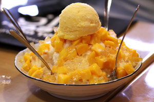 A plate of shaved ice in Taipei. Here, shown with condensed milk, mango cubes and topped with a scoop of ice cream.