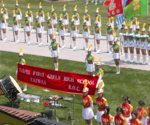The drum and brass band in red and white, the marching team in green and white. These are the famous Bei Yi Nu Marching Team girls.
